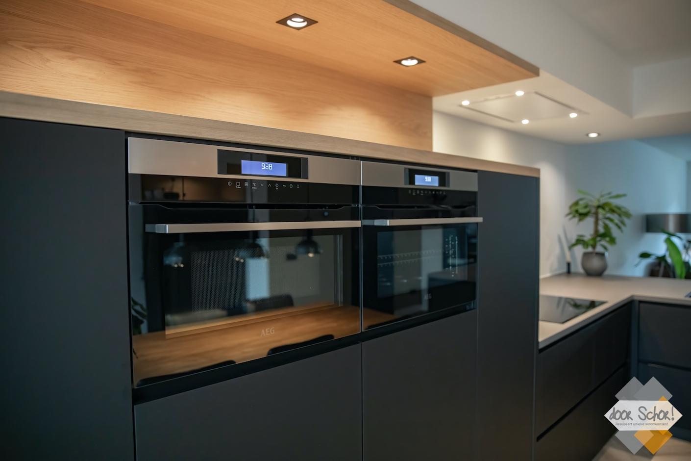 keuken op maat in het matzwart met eikenhout gecombineerd met daarin keukenapparaten