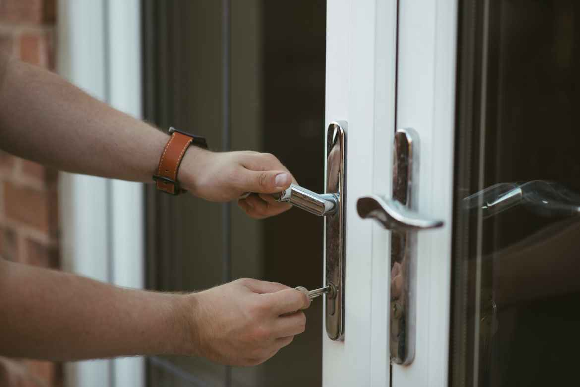person holding door lever and key