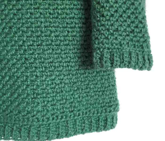 Corner of green crochet moss stitch sweater hanging on white wall