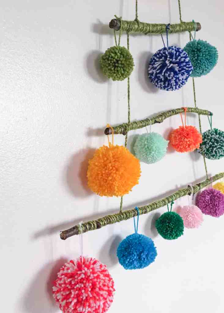 Pom Poms hanging from horizontal sticks on white wall strung together to make a tree shape