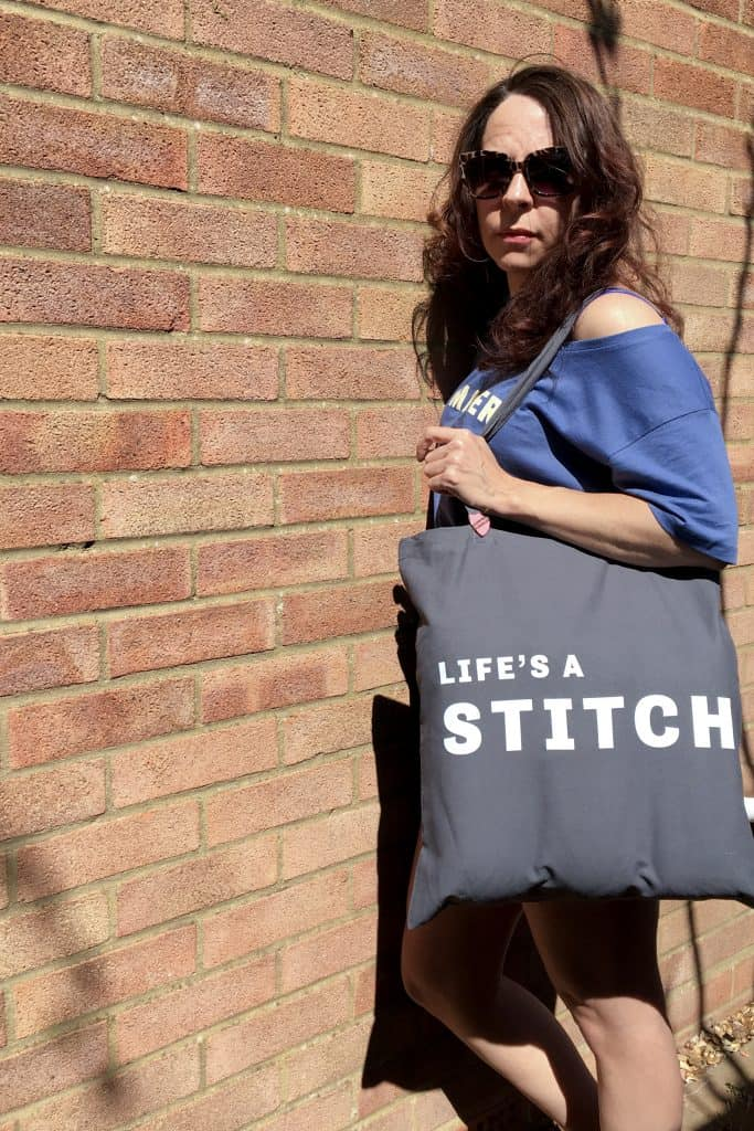 Woman holding grey cotton tote with Life's a stitch slogan