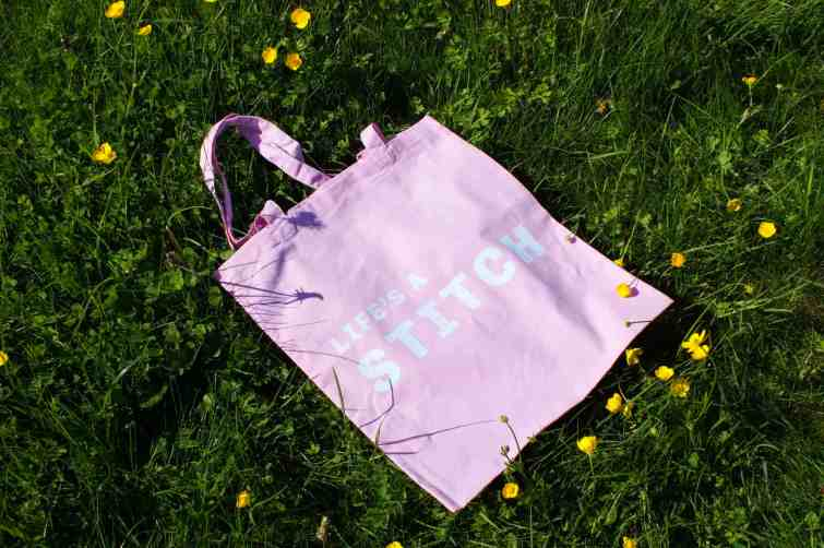 Life's a stitch pink cotton slogan tote on meadow