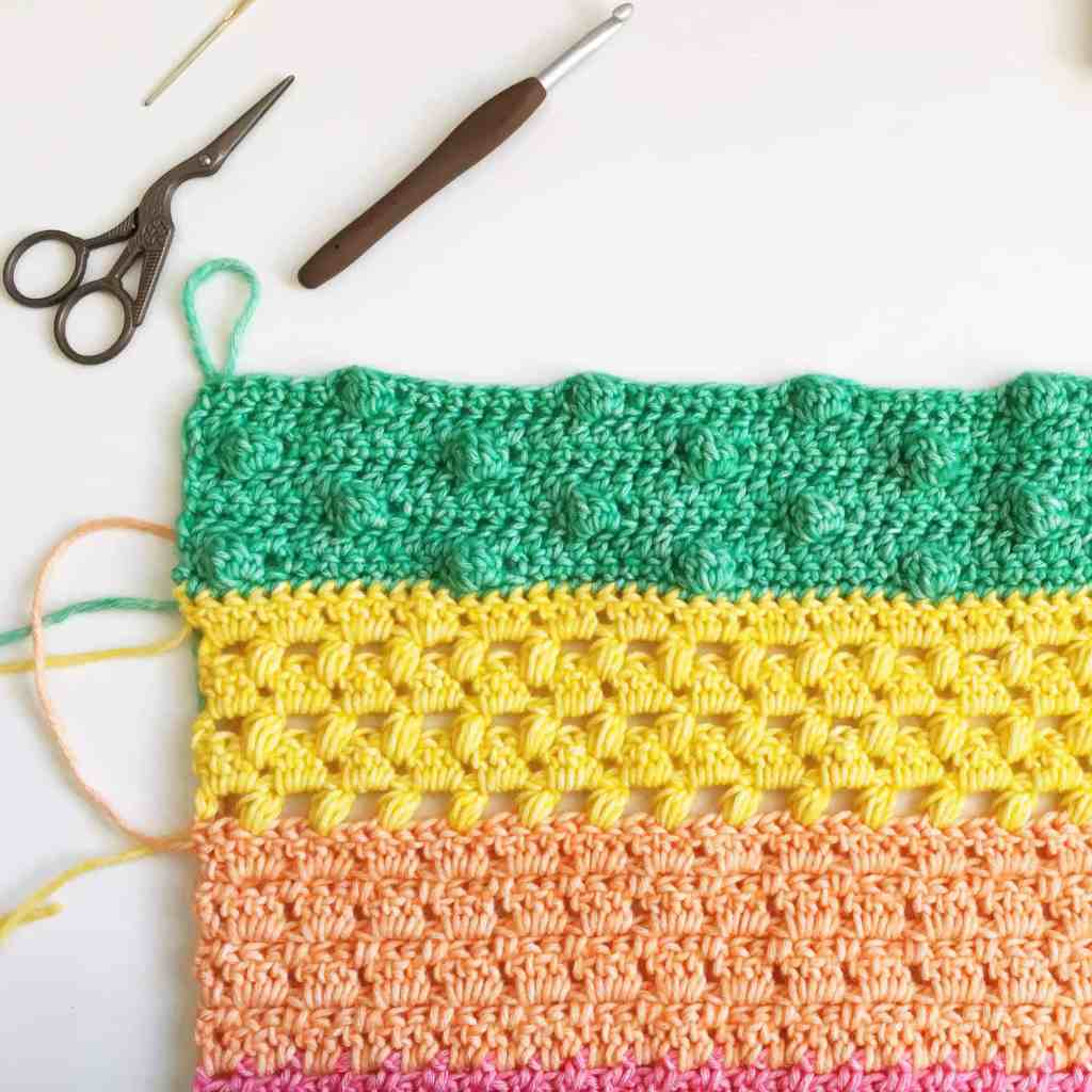 A close up of a piece of fabric made from different crochet stitches in green yellow orange and pink yarn with a hook and pair of scissors lying by it's side on a white surface