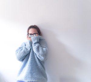 Woman in blue cosy crochet alpaca silk roll neck sweater leaning against white wall
