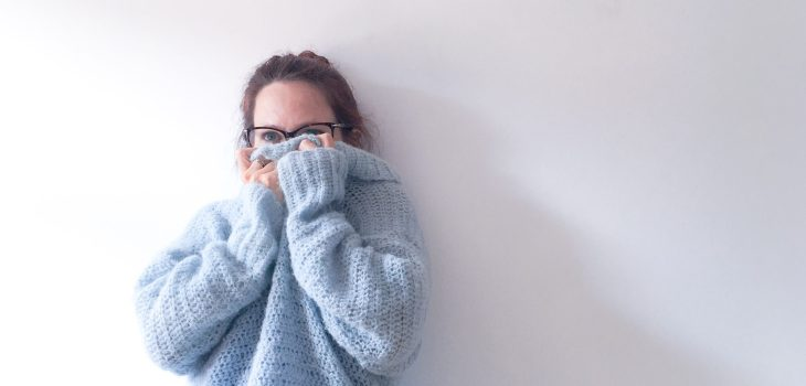 Woman in blue cosy crochet alpaca silk roll neck sweater leaning against white wall