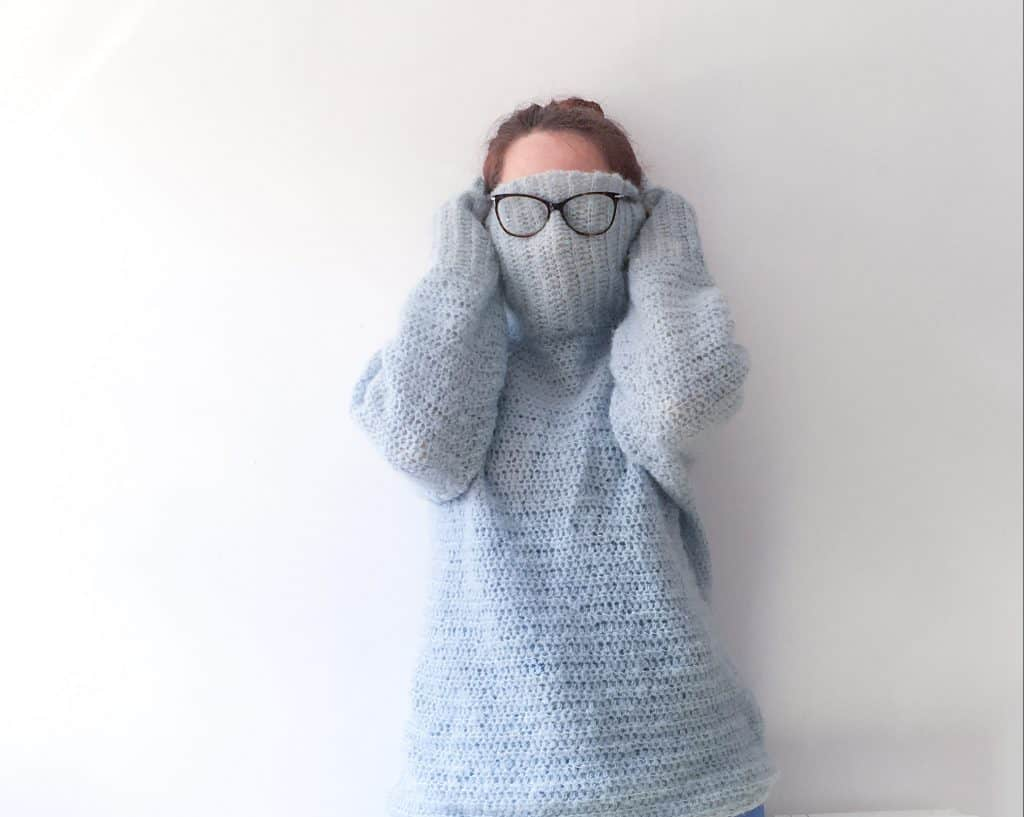 Woman hiding in roll neck sweater with glasses