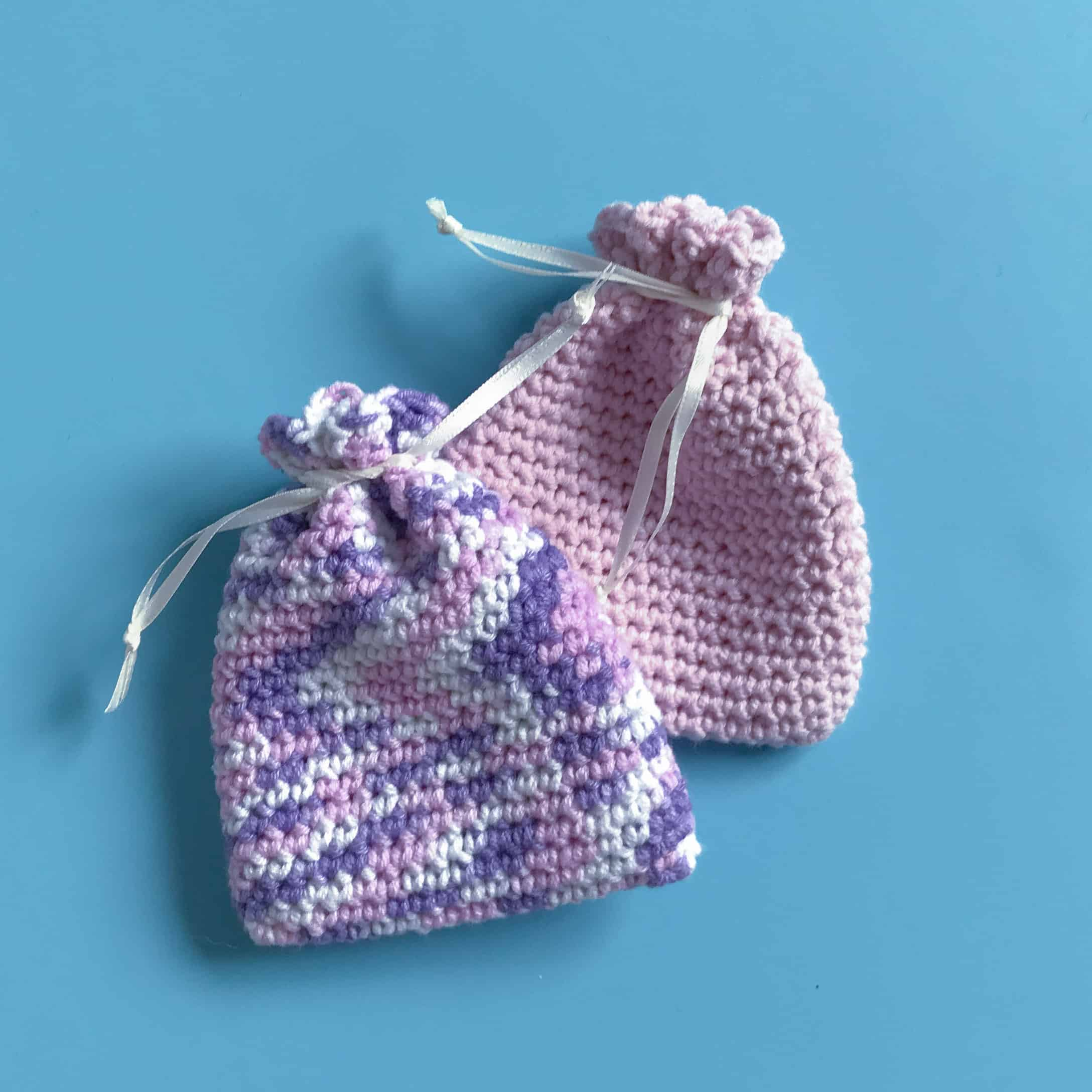 2 Finished Crochet Favour Bags in pink and purple on blue background