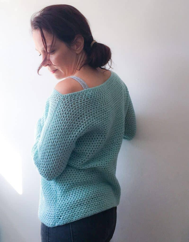 woman wearing off shoulder crochet sweater