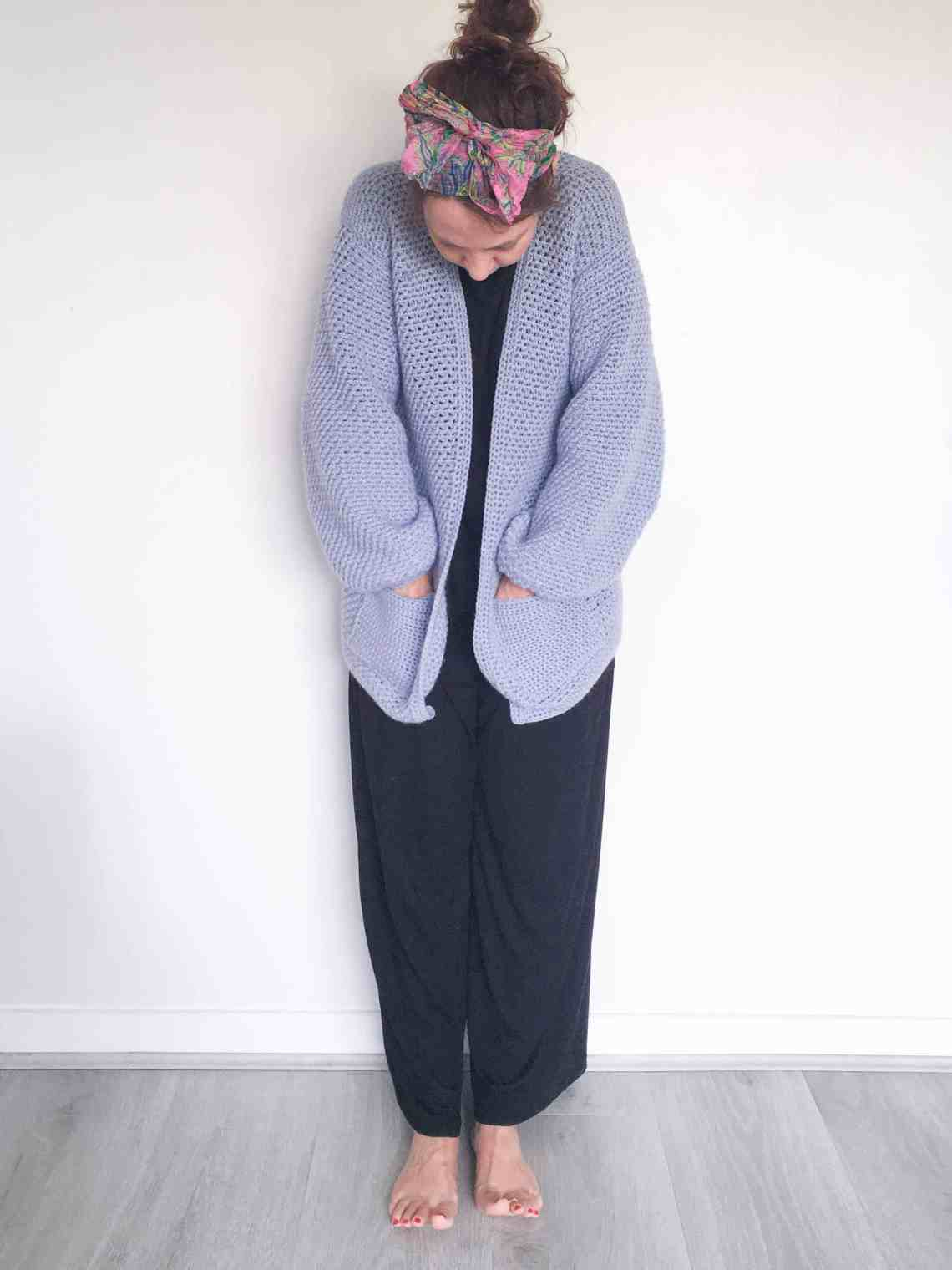 Woman in crochet cardigan looking at toes