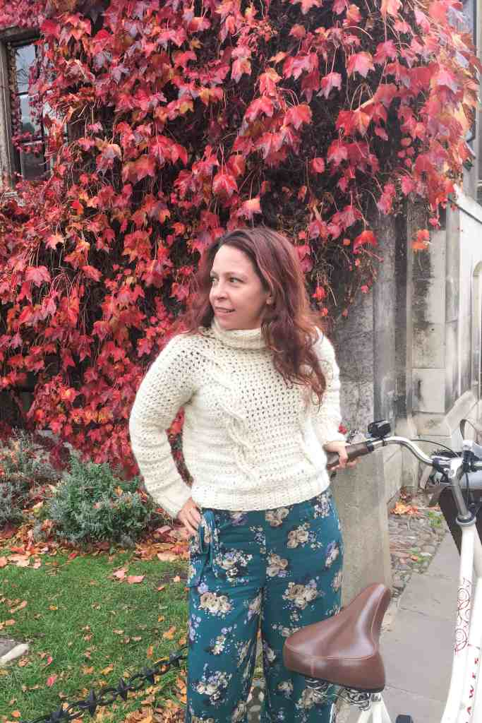 Girl in cable knit jumper with bile in front of red ivy in cambridge