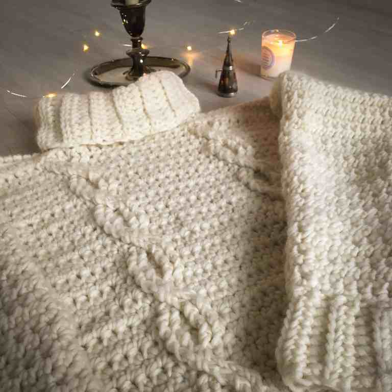 Cabled roll neck crochet sweater with fairy lights and candles