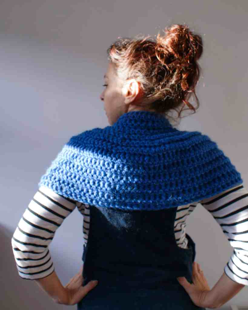 Back of woman wearing blue crochet cowl stripy top with Lucy and Yak pini