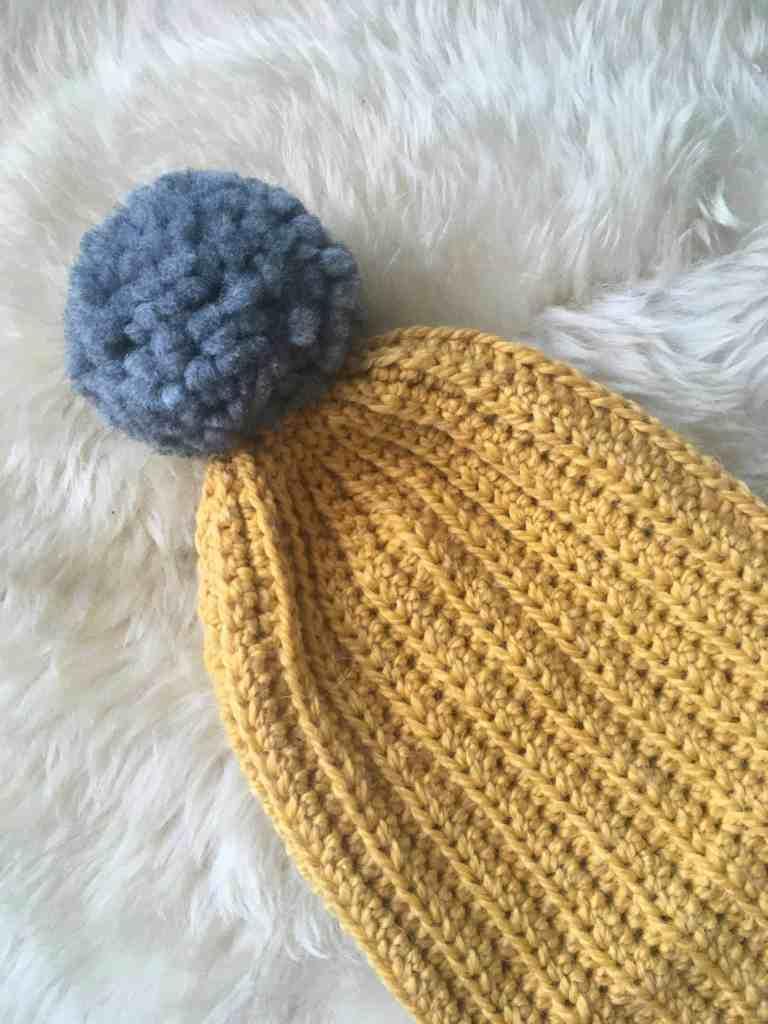 Mustard ribbed crochet beanie with grey pom pom