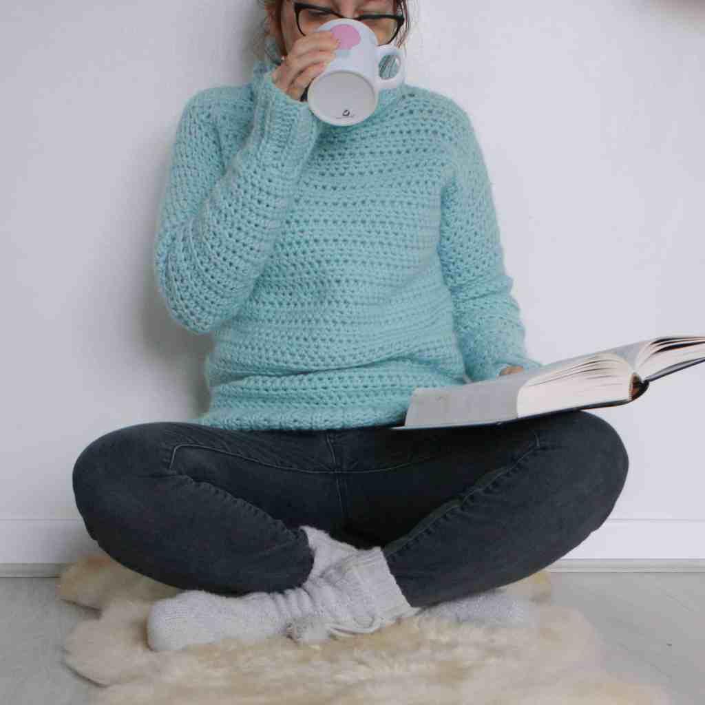 Woman reading drinking tea in cosy crochet sweater