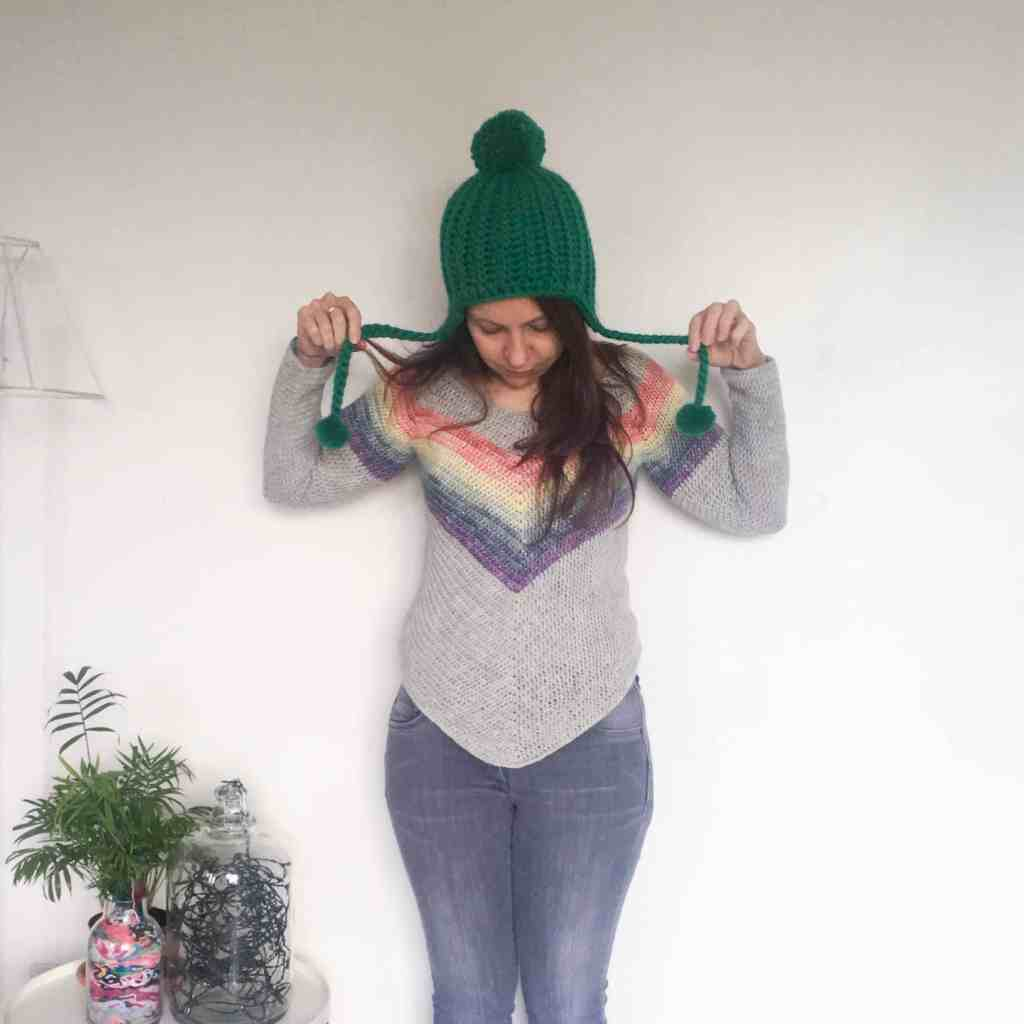 Woman in green crochet pompom hat and rainbow jumper