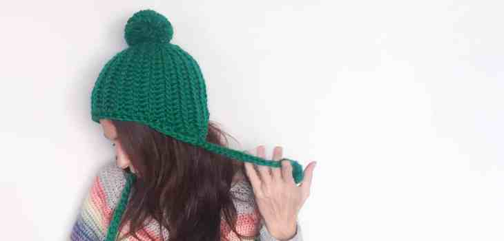 Side view of green crochet pom pom hat