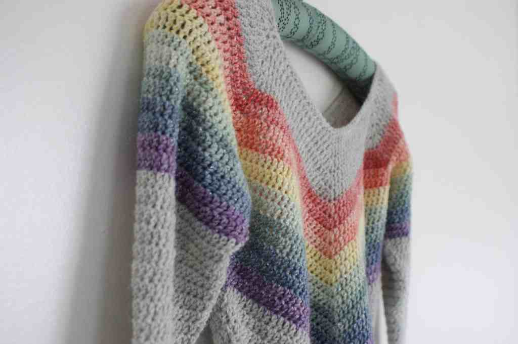 sparkly rainbow crochet sweater hanging on white wall