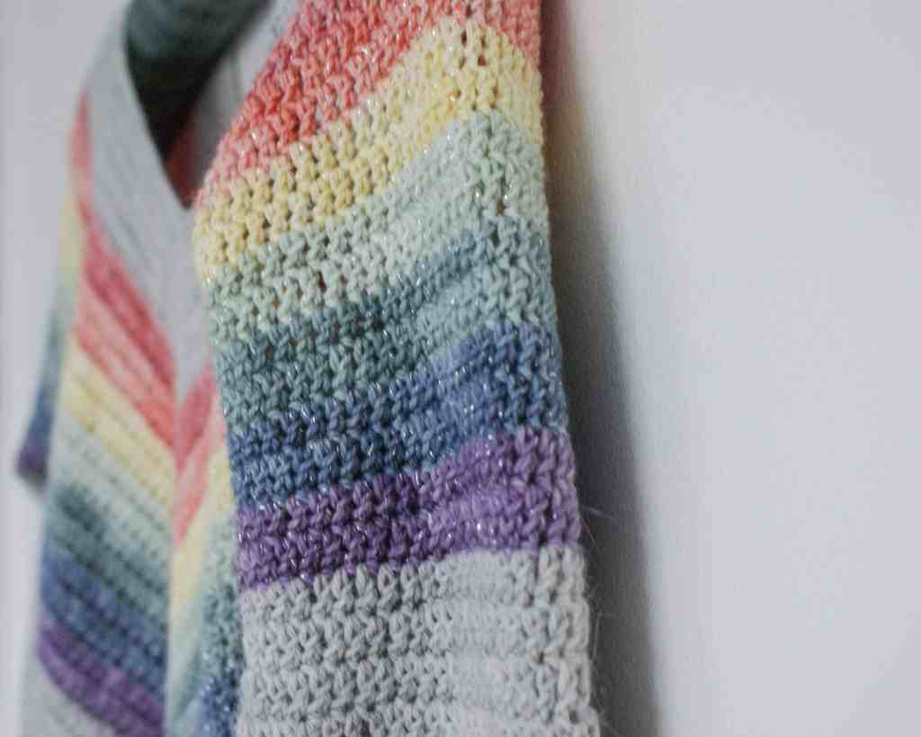 Close up of Crochet Rainbow Sweater hanging on white wall