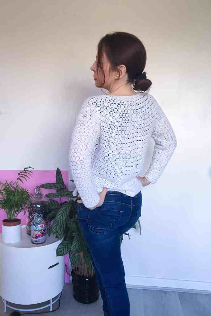 back of a woman wearing a white crochet cardigan