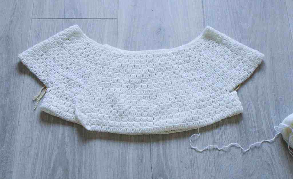 Part made crochet cardigan in cream wool on grey background