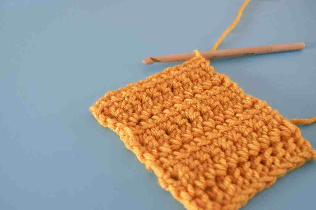 Yellow linked double crochet swatch with wooden crochet hook on blue background
