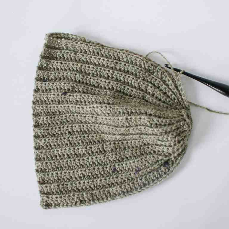 Black Crochet hook and green yarn making crochet hat