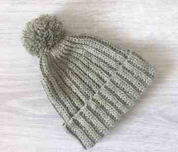 Olive green ribbed crochet beanie hat with pom pom on grey wood backgorund
