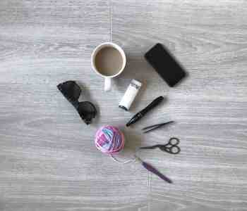 Assorted crochet tools with sunglasses, phone and cup of tea on grey wood floor