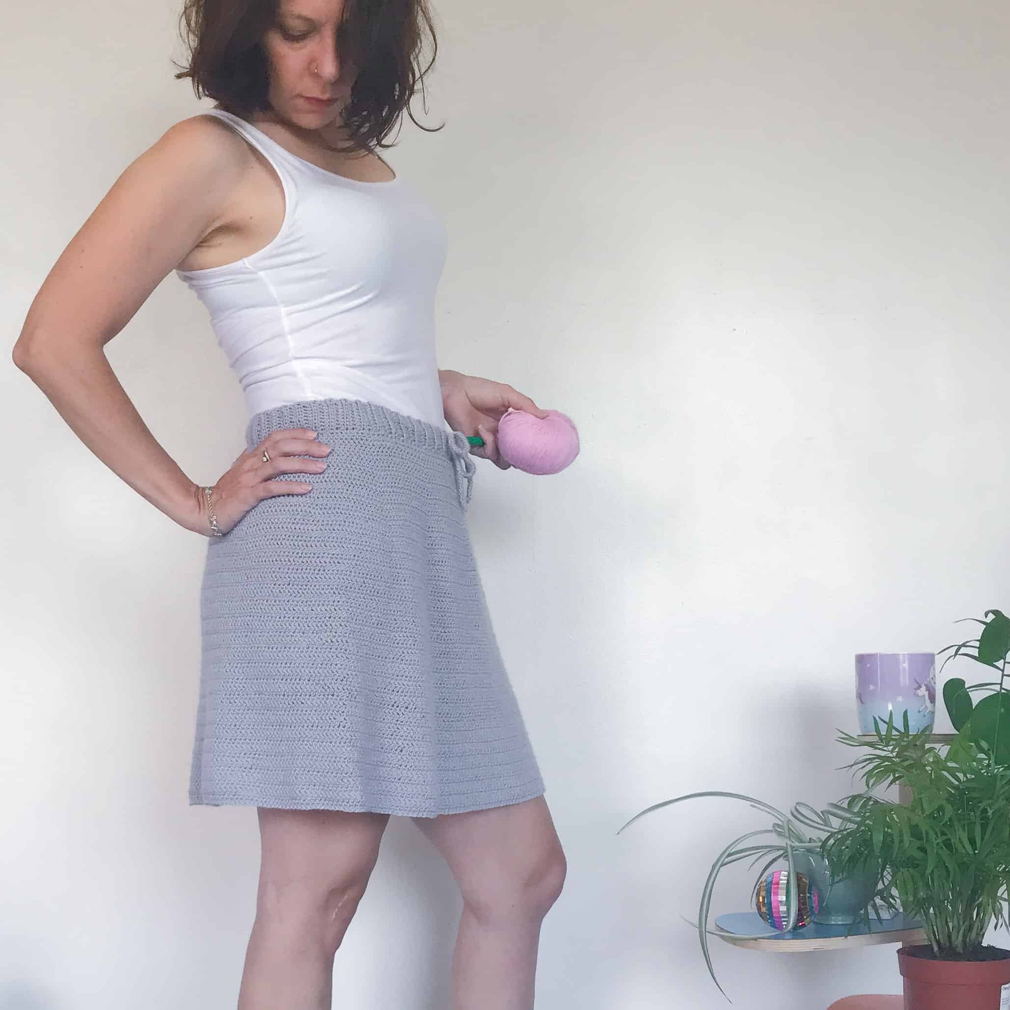 Woman wearing grey crochet skirt and white vest holding a pink back of yarn in one hand whilst the other rests on her hip