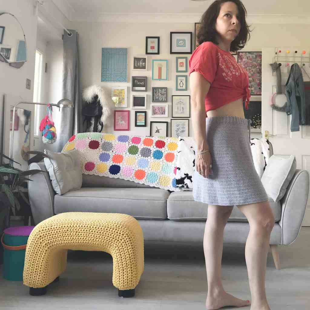 Woman in grey crochet skirt and red cropped tee standing in front of sofa and gallery picture wall