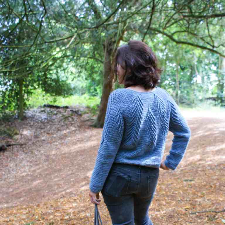 A woman standing in a wood wearing a blue crochet sweater with her back to camera
