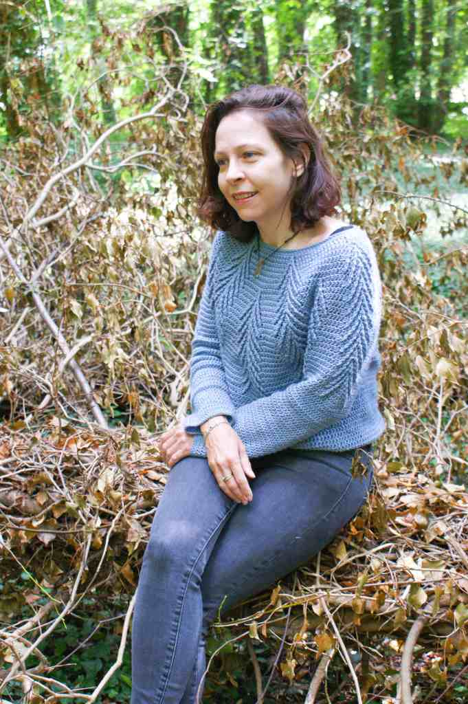 A woman sitting on a fallen tree trunk wearing a blue crochet cabled sweater