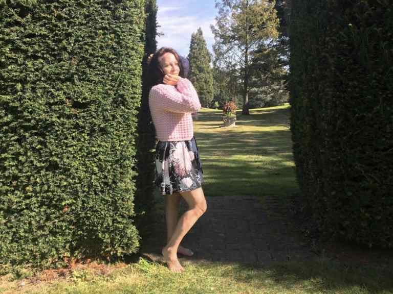 Woman in pink crochet cardigan standing by hedge