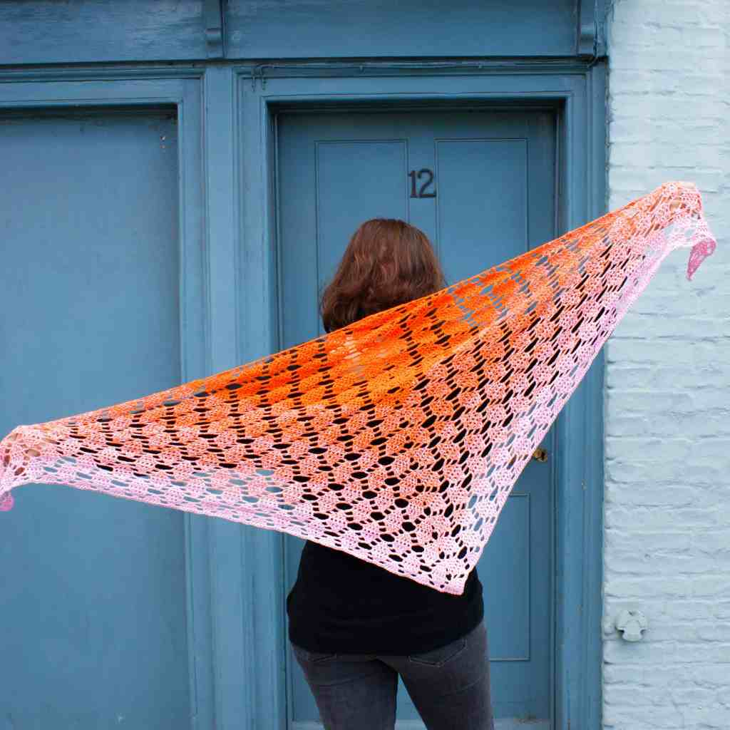 Woman standing in front of blue door with back to camera holding pink and orange crochet scarf at an angle