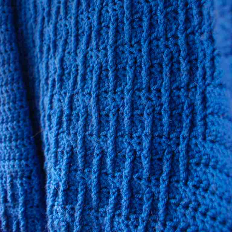 Blue textured crochet fabric close up
