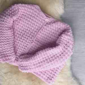 Pink crochet cardigan laying on sheepskin rug