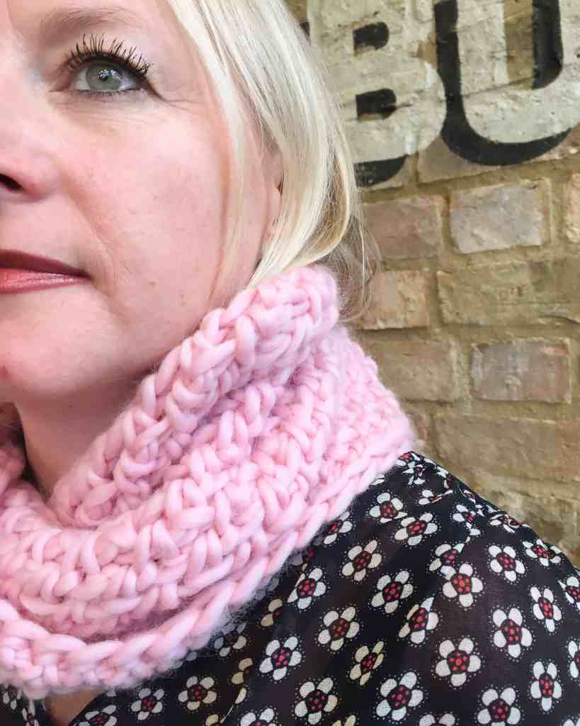 Blonde woman with half face seen wearing pink crochet cowl in front of brick wall
