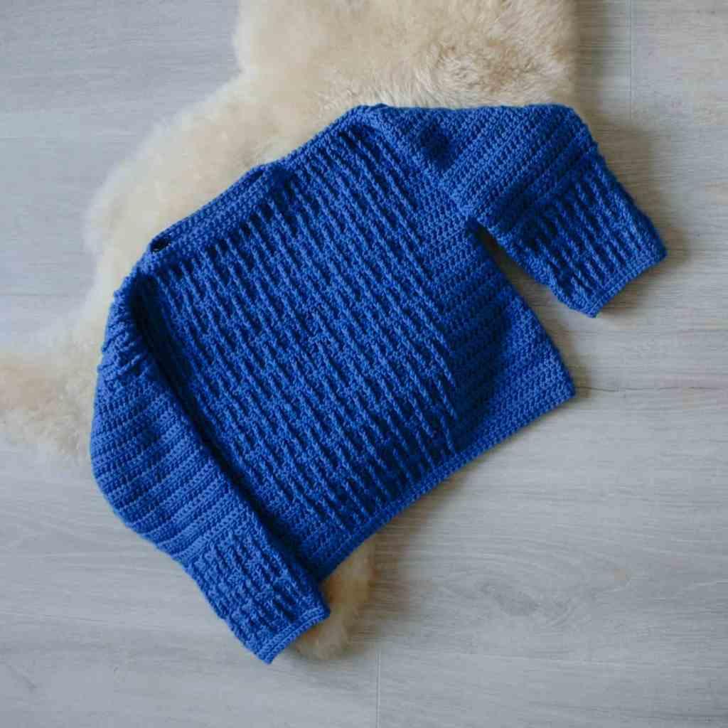 Flatlay image of blue crochet sweater on sheepskin rug
