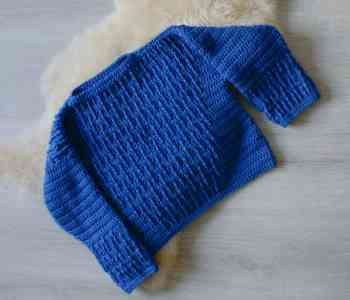 Flatlay image of blue crochet sweater on sheepskin rug