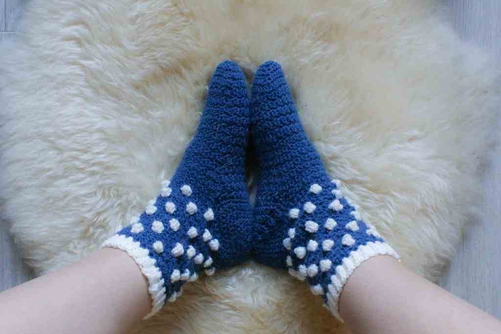 Picture of feet in blue crochet socks with white bobbles on the ankle imitating snowballs stood on sheepskin rug