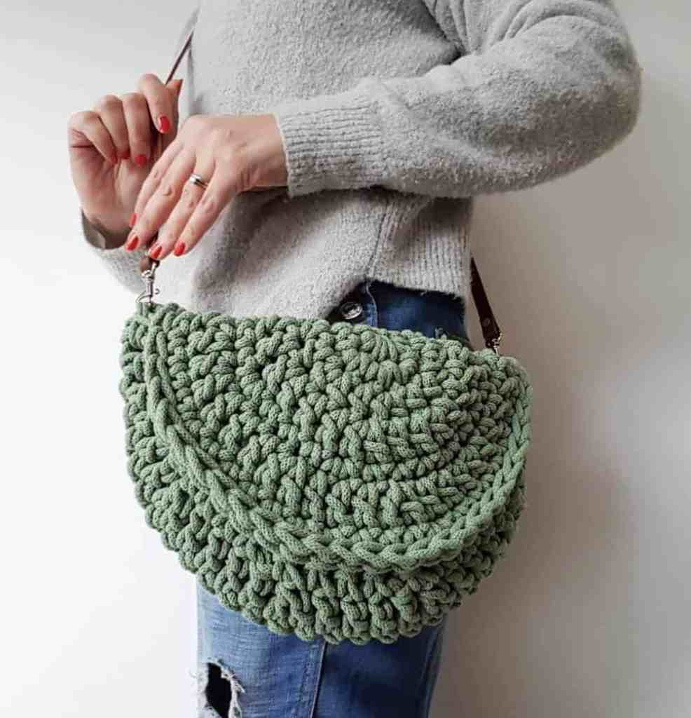 green cotton crochet half moon bag being worn by woman in grey sweater and torn jeans