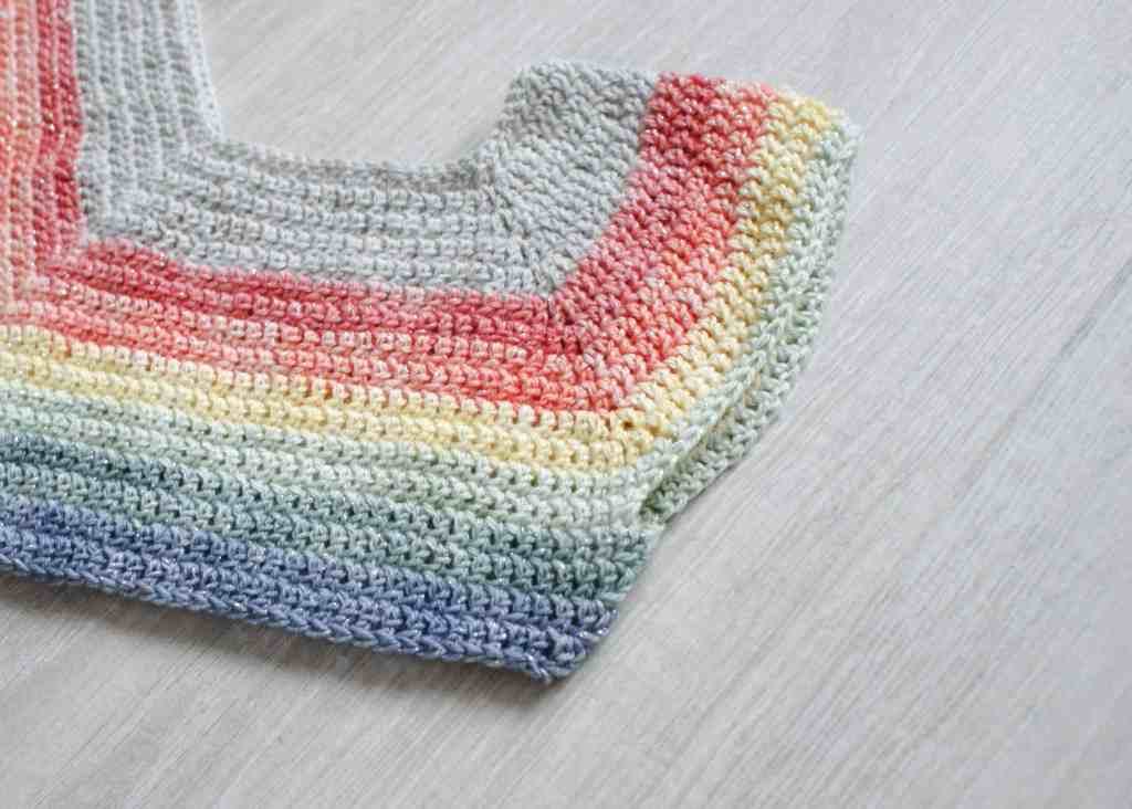 Top down rainbow crochet sweater in progress laid flat on grey floor