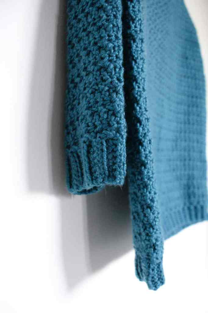 close up of the sleeve of a teal crochet sweater hanging on a white wall