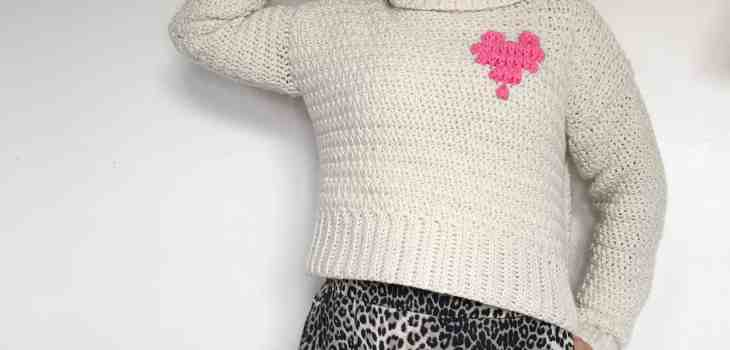 woman wearing cream roll neck crochet sweater with a pink heart motif on it