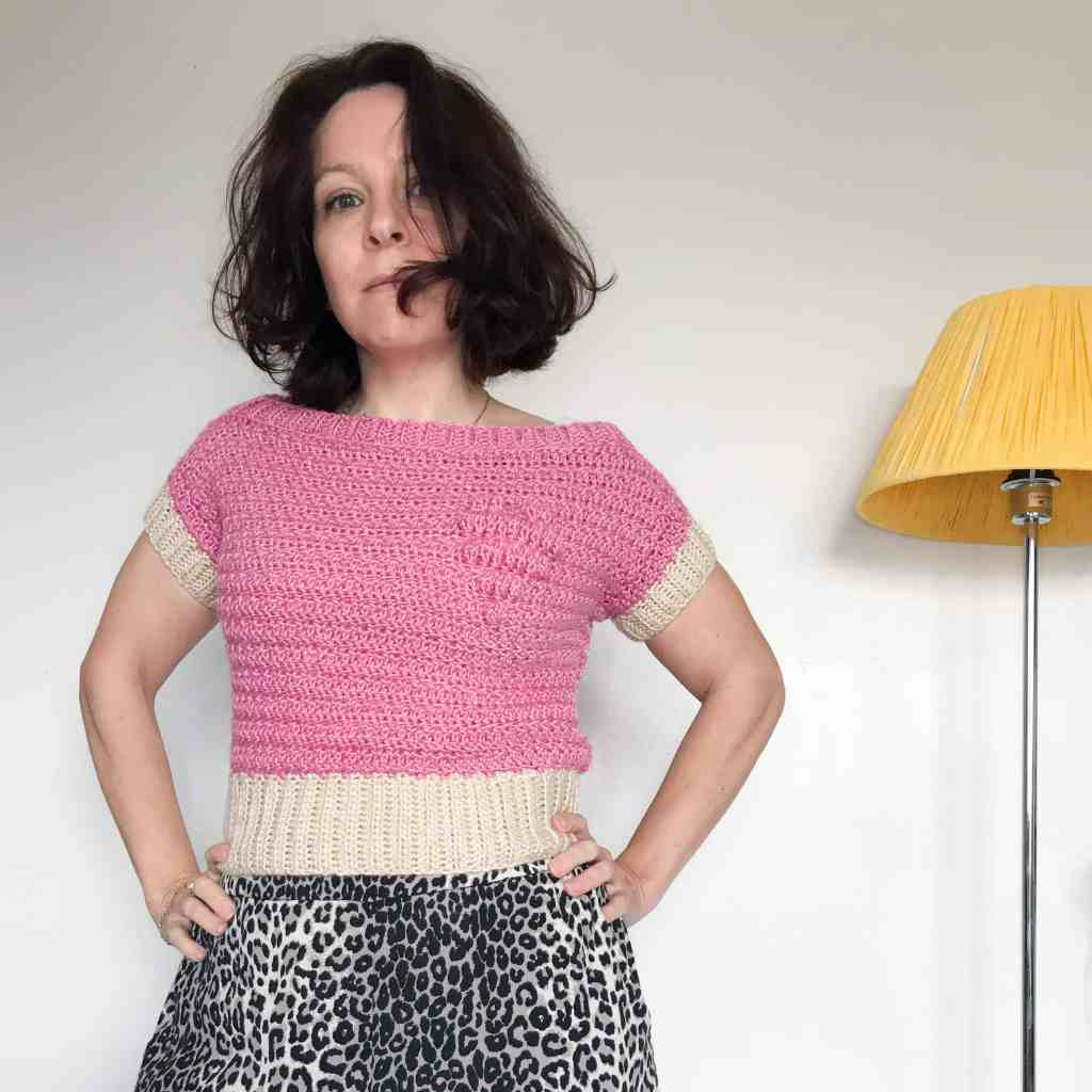 Woman in pink crochet t-shirt with bobble heart motif. Her hands are on her hips as she stands next to a lamp with a yellow shade in front of a white wall
