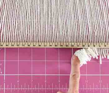 A finger wipes away the cut ends of a yarn fringe