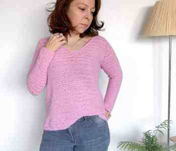 A woman stands in front of a white wall wearing a pink crochet sweater and grey jeans
