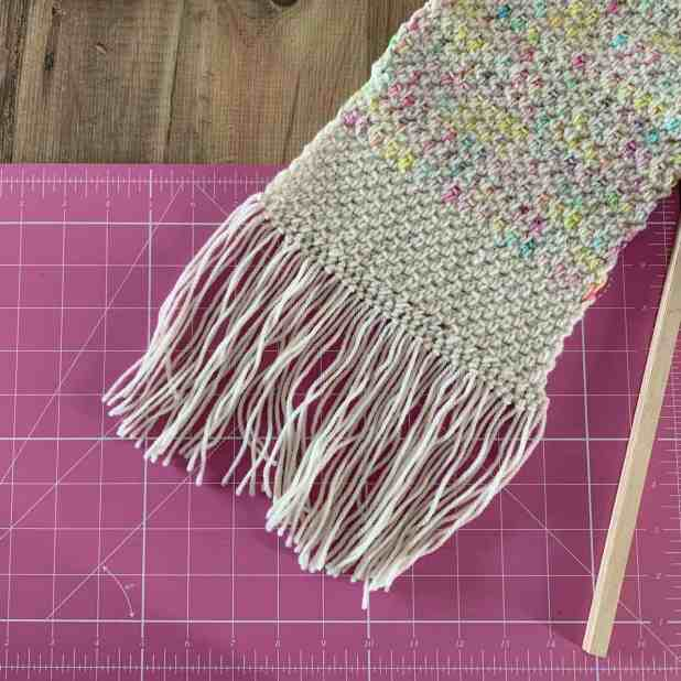 The end of a cream crochet scarf with wonky fringe lies on a pink cutting mat