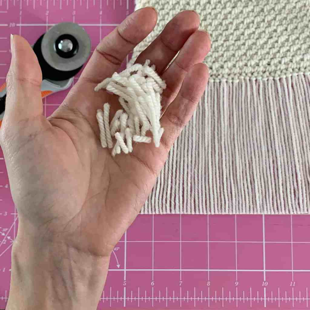 A hand holds the cut yarn ends above a neatly cut scarf fringe with a rotary trimmer laying on a pink cutting mat
