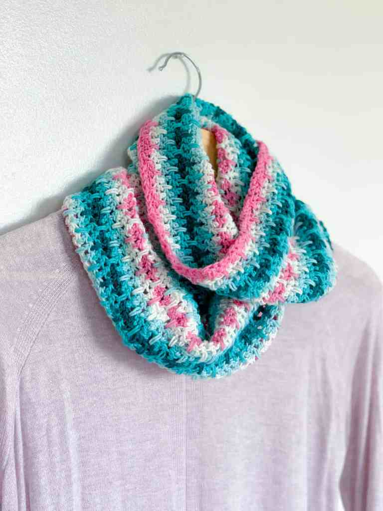 Pink, White Blue and Turquoise stripe crochet infinity scarf on a hanger with a sweater hanging from it